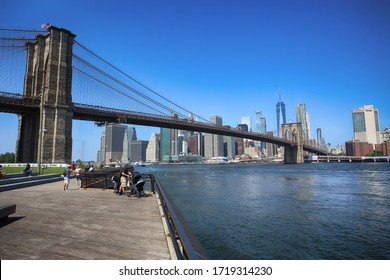 New York, USA – August 23, 2018: People enjoying and view of scene of the Brooklyn bridge and Manhattan Skyline, seen from Empire Fulton Ferry Park.