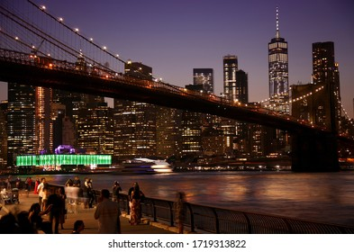 New York, USA – August 25, 2018: People enjoying the evening view of night scene of the Brooklyn bridge and Manhattan Skyline at Night, seen from Empire Fulton Ferry Park.