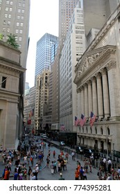 NEW YORK, USA - August 5, 2014: From Federal Hall, pedestrians walk along Broad Street past the New York Stock Exchange. The Exchange building was built in 1903.