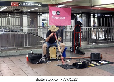 NEW YORK, NEW YORK, USA - AUGUST 6: Subway performer blows into a didgeridoo.  Taken August 6, 2017 in New York.