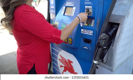 New York, USA - Circa 2018: Unidentifyable woman in red shirt swipe credit card into Mobile gas station fuel pump to pay for gasoline to fill car tank