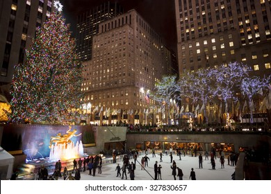 New York, New York, USA - December 10, 2012: The Rockefeller Center Christmas Tree shines brightly as people ice skate below on the famous Rockefeller Center rink in the evening.