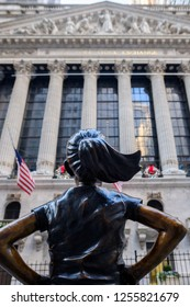New York, USA - December 11, 2018 - The Fearless Girl statue facing The New York Stock Exchange NYSE building in Lower Manhattan, New York City