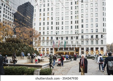 New York, New York, USA - December 11, 2015: Grand Army Plaza and the Plaza Hotel in Manhattan. People can be seen on Grand Army Plaza. Wreaths  on Plaza Hotel Windows reflect the Christmas season.
