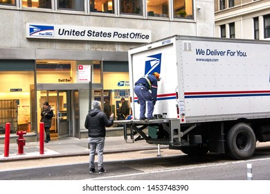 NEW YORK, USA - DECEMBER 14, 2018: USPS postman on a mail delivery truck in New York. USPS is an independent agenc of US federal government responsible for providing postal service in the US.