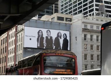 New York, USA - December 2010: Huge advertising billboard of iTunes Apple store with the Beatles (John Lennon, Paul McCartney, Ringo Starr, George Harrison) on Brooklyn Bridge.Music streaming service