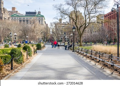 New York, USA - December 30, 2014: People enjoying a sunny winter day in Washington Square Park. The park, in the neighborhood of Greenwich Village is a meeting place and center for cultural activity.