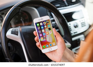New York, USA - February 01, 2018: Female hand using iPhone 8 Gold in a car.