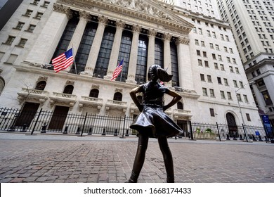 """NEW YORK, USA - FEBRUARY 02, 2020: The """"Fearless Girl"""" statue standing at its new location facing the New York Stock Exchange."""