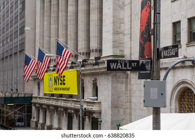 NEW YORK, USA – JANUARY 15 2017: A close-up shot of a Wall Street road sign and the Stock Exchange Building in the background.