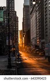 NEW YORK, USA – JANUARY 15 2017: Vertical view of golden sun rays showing in between the empty avenues filled with tall buildings.
