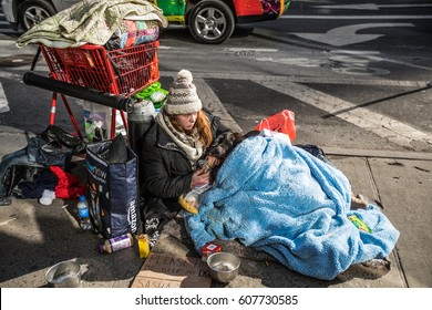 New York, USA - January 17, 2017: homeless woman sitting on the street in the city center covered with a blanket with her possessions lying next to her.