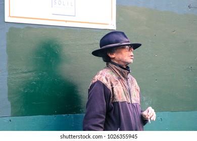 New York, USA, January 2018, Man standing against wall smoking