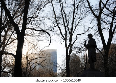 New York, New York / USA - January 9, 2010: A silhouette of bronze statue of the 7th Regiment Memorial stands backlit by ethereal light with leafless winter tree and a New York cityscape.