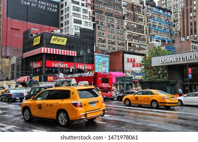 NEW YORK, USA - JULY 1, 2013: People walk along rainy 8th Avenue in New York. Almost 20 million people live in New York City metropolitan area.