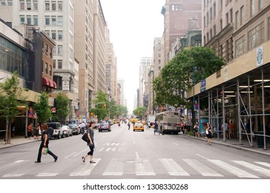 New York, New York / USA - July 13, 2010: People crossing a street intersection on a designated pedestrian lane.