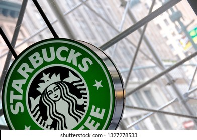 New York, New York / USA - July 13, 2010: Artistically skewed and partially framed Starbucks store outlet logo by the glass store window looking out to scaffoldings and busy street of 5th Ave in NYC.