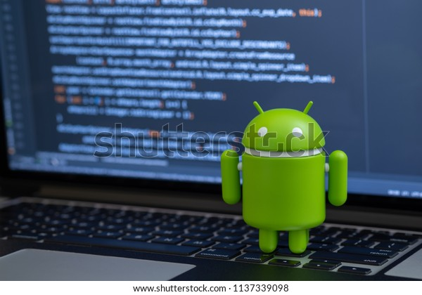 New York, USA - July 2, 2018 - Google Android figure standing on laptop keyboard with code in background