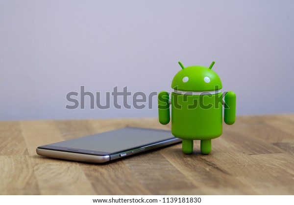 New York, USA - July 2, 2018 - Google Android figure standing next to smart phone