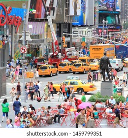 NEW YORK, USA - JULY 3, 2013: Tourists and local people visit Times Square in New York. The square at junction of Broadway and 7th Avenue has some 39 million visitors anually.