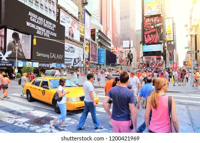 NEW YORK, USA - JULY 4, 2013: People visit Times Square in New York. Times Square is one of most recognized landmarks in the world. More than 300,000 people pass through Times Square daily.