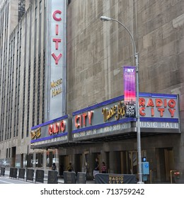 NEW YORK, USA - JULY 4, 2013: People walk past Radio City Music Hall at 6th Avenue in New York. Radio City exists since 1932 and is registered in U.S. National Register of Historic Places.