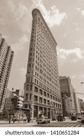 NEW YORK, USA - JULY 5, 2013: People walk by Flatiron Building in New York. Flatiron is one of the most recognizable buildings in NY and is considered National Historic Landmark.