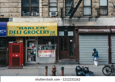 New York, USA - June 01, 2018: Woman standing on a street next to a Deli in Harlem, NYC. Since the 1920s, Harlem has been known as a major African American residential, cultural and business center.