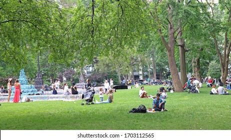 New York, USA - June 05, 2019: People enjoying nice weather on the loan of Central park in New York city. People having nice time with their children, family and friends in nature.