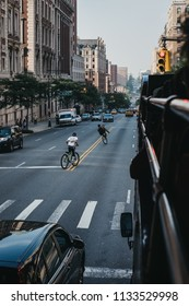 New York, USA - June 1, 2018: Teenagers riding bikes on the road in Harlem, New York. Since the 1920s, Harlem has been known as a major African American residential, cultural and business center.