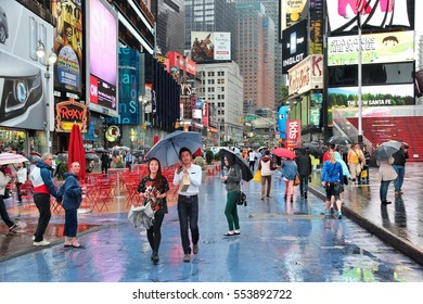 NEW YORK, USA - JUNE 10, 2013: People visit rainy Times Square in New York. The square at junction of Broadway and 7th Avenue has some 39 million visitors anually.