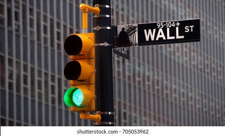 NEW YORK, USA - JUNE 12, 2010: View of traffic lights with black and white pointer guide in Wall Street, New York City. Green traffic light to Wall street banks money dollars finance offices.
