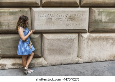 New York, USA - June 18, 2016: Federal Reserve Bank of New York sign with young woman on mobile phone