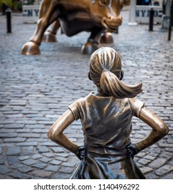 NEW YORK, USA - JUNE 20, 2018: The famous metal sculpture The Fearless Girl by the Wall Street in Lower Manhattan at sunset.