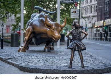 "New York, USA - June 25, 2017 - ""The Fearless Girl"" statue facing Charging Bull in Lower Manhattan, New York City"