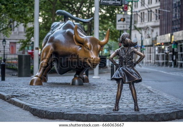"New York, USA - June 25, 2017 - ""The Fearless Girl"" statue facing Charging Bull in Lower Manhattan, New York City"
