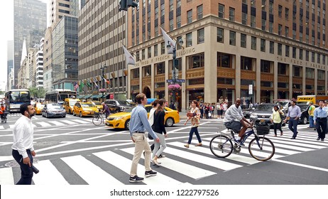 New York, USA - June 28. 2016: Yellow cabs and heavy traffic in 5th avenue with pedestrians crossing