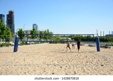 New York, USA - June 3, 2019: Group of people play volleyball in Gantry Plaza State Park in Queens