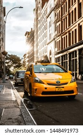 New York / USA - June 30 2019: Yellow taxi on the street. Classic buildings and Sun flare on the back ground
