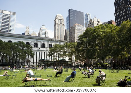 New York, New York, USA - June 30, 2011: People enjoying the sunny weather on the Bryant Park lawn in Midtown Manhattan. Bryant Park sits behind the New York Public Library on 6th Avenue.
