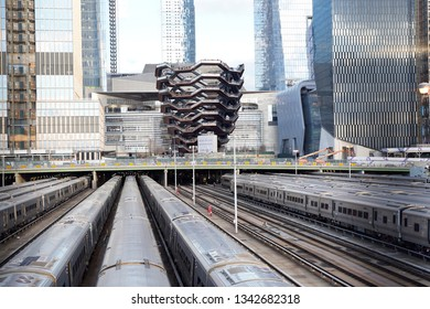 New York, New York / USA - March 16 2019: Vessel  (TKA), a spiral staircase, with railroad and trains in front, skycrappers behind,  Hudson Yards, Manhattan's West Side, NYC.
