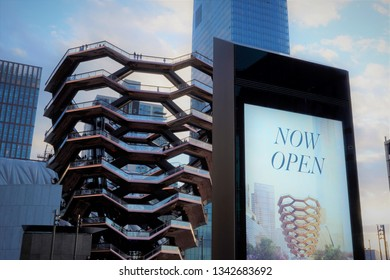 New York, New York / USA - March 16 2019: Vessel  (TKA), a spiral staircase, opened, with people standing inside, mall near it, skycrappers behind, Hudson Yards, Manhattan's West Side, NYC.