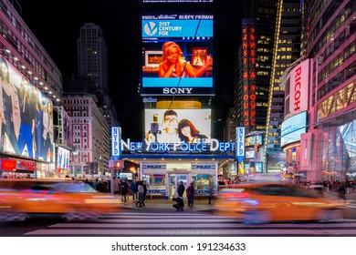 NEW YORK, USA - MARCH 16: Symmetrical composition of New York Police Department on Times Square at night with neon lights, with people and taxis, yellow cabs, on March 16, 2014 in New York, USA.