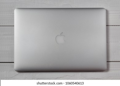 New York, USA - March 27, 2018: Closed silver macbook pro on wooden table top view.