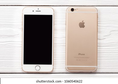 New York, USA - March 27, 2018: Iphone smartphone front and back side on wooden background. Iphone with black blanck screen top view.