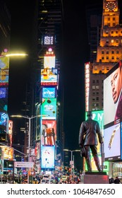 NEW YORK, USA - MARCH 3, 2018: View of statue of George m. Cohan at Times Square New York and street signs, advertisements boards at night in background.
