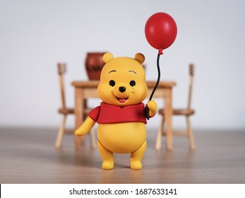 New York, USA - March 30, 2020: Winnie the Pooh holding red balloon to show everyone.
