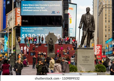 NEW YORK, USA - MARCH 6, 2018: View of statue of George m. Cohan and Tourists on the famous red stairs in Times Square New York