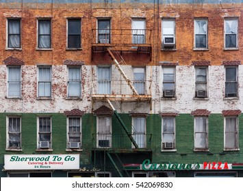 NEW YORK, USA - May 01, 2016: Facade of an old building in Manhattan. Brick wall with peeling off paint and escape fire ladders