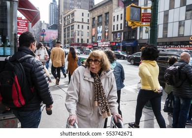 NEW YORK, USA - May 03, 2016: Manhattan street scene. New Yorkers in Manhattan in a hurry about their business. Senior woman using a walker
